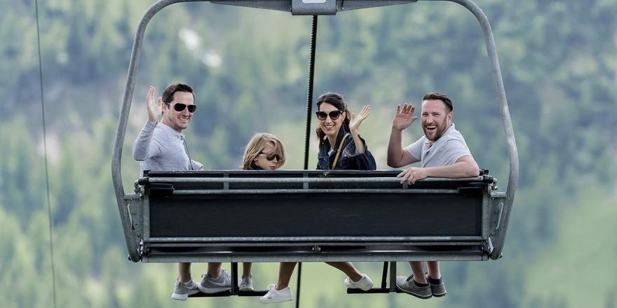 Familie fährt mit der Bergbahn ins Wandergebiet
